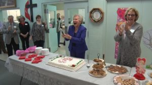 woman standing in front of a cake and exclaiming while others look on
