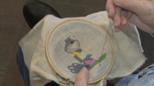 close up of someone working on a cross-stitch project