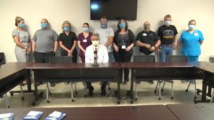 Macon County hospital employees standing behind a conference table