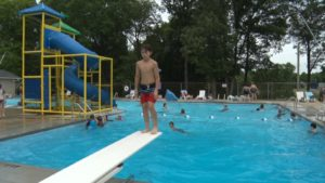 a boy stands facing backwards on the end of a diving board