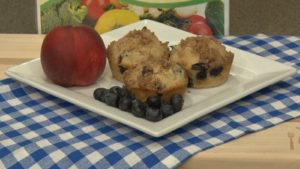 muffins on a plate with blueberries and a peach