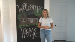 Chrissy Jenkins standing in front of a house with a chalkboard drawing of a house, with Welcome Home written on it.