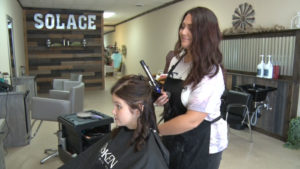 Hairdresser curling a young girls hair at the Solace salon.