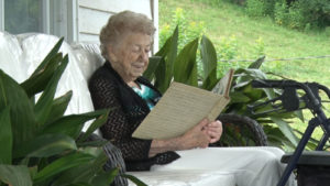 Annette Cothron sitting on a bench outside her house looking at a photo album.
