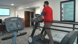 Man walking on treadmill while wearing a mask.
