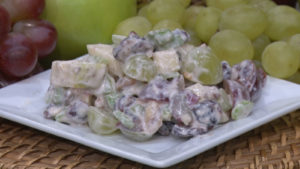 apple cranberry waldorf salad on a plate next to grapes