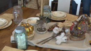 table with plates, and corn, and a turkey statue