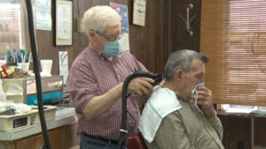 Fred Steen at barber shop cutting customer's hair while wearing masks