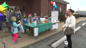 Young Girl Scouts selling cookies outside wearing masks