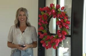 Chrissy Jenkins standing next to rose wreath on door
