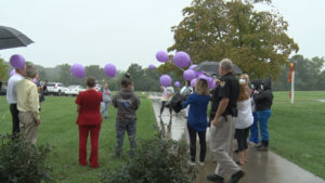 people walking with purple balloons outside